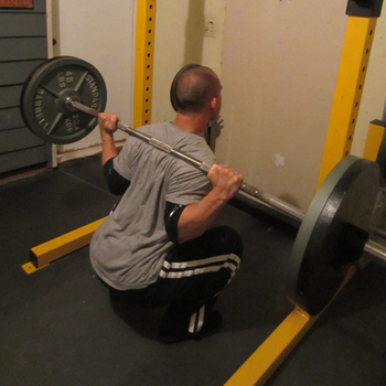 Jarlo presses barbell squat in gym