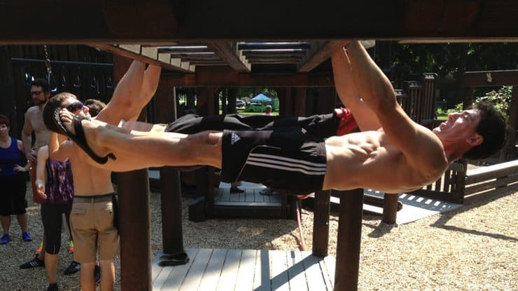 trainers perform front levers at a park