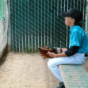 Young baseball player sitting on the sidelines