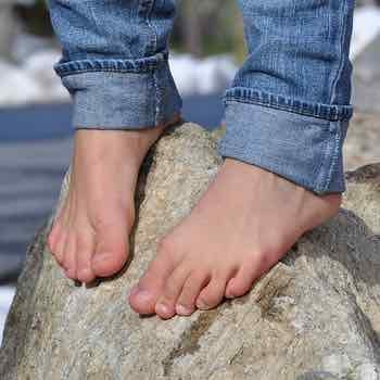 Bare feet standing on a rock outside