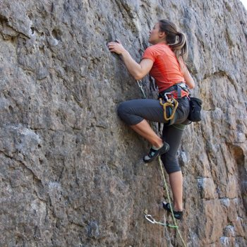 female athlete rock climbing the side of a mountain