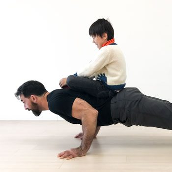 Ryan performing a push-up with his kids