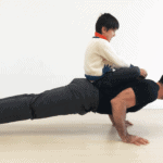 kid on dad doing pushups
