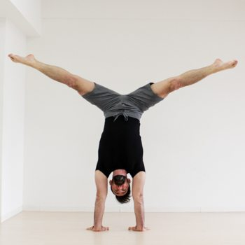 Ryan Hurst practicing a straddle handstand