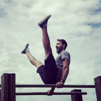 Ryan Hurst practicing a v sit on parallel bars