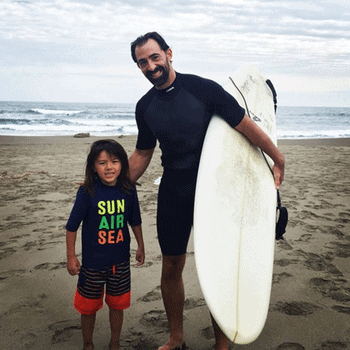 Ryan is teaching his son Shion how to surf