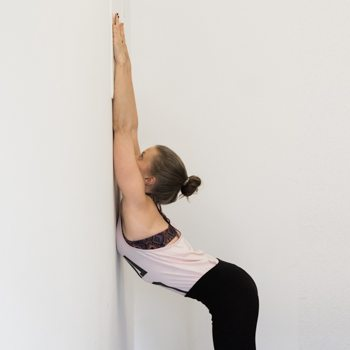 Alicia stretching spine against a wall