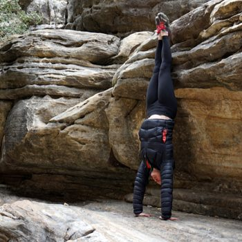 athlete performing a handstand outdoors against boulders