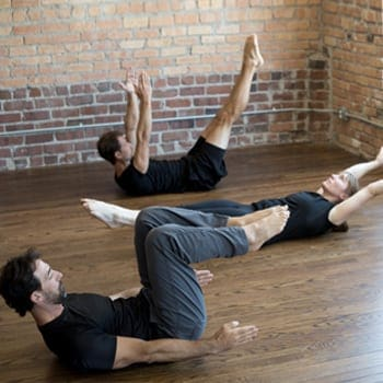 Group of people doing hollow body holds