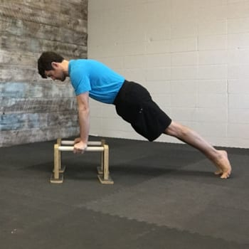 Jeff doing plank exercise on parallettes