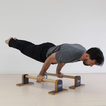 Ryan doing an arm lever exercise on parallettes