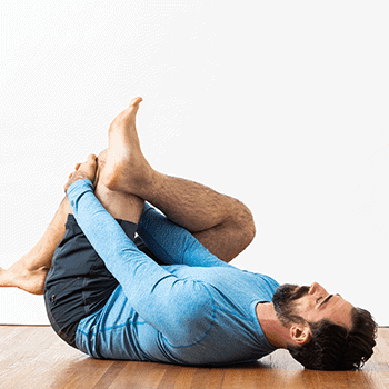 lying on floor pulling leg into chest hamstring stretch