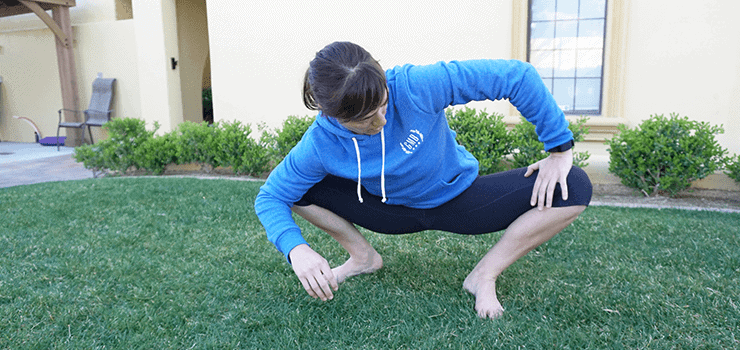 woman stretching hip in squat