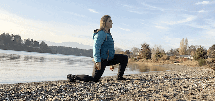 woman doing lunge stretch on beach