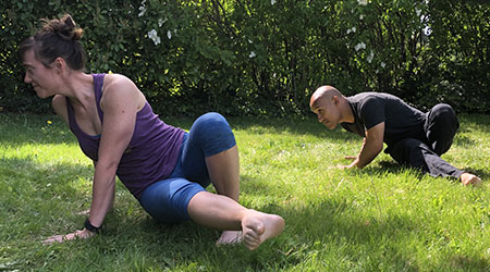 A woman and a man practicing controlled movement outdoors